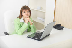 Young woman with laptop sits at light office. The young woman with the laptop sits at a table at light office stock images