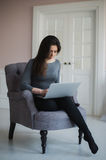 Young woman with laptop sitting on armchair at home Royalty Free Stock Photo