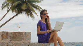 Young woman with laptop is sitting on the beach and talking on the phone. stock video