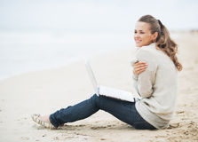 Young woman with laptop sitting on beach Royalty Free Stock Photo