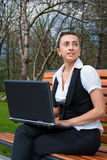 Young woman with laptop sitting on bench Stock Photo