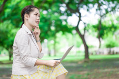 Young woman with laptop sitting on bench Royalty Free Stock Image