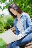 Young woman with laptop sitting on bench in park Royalty Free Stock Images