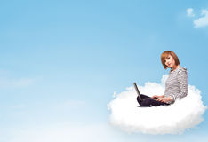 Young woman with laptop sitting on cloud with copy space Stock Images