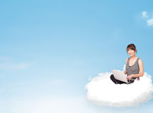 Young woman with laptop sitting on cloud with copy space Royalty Free Stock Photo