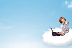 Young woman with laptop sitting on cloud with copy space Royalty Free Stock Photos