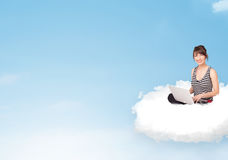 Young woman with laptop sitting on cloud with copy space. Pretty young woman with laptop sitting on cloud with empty space Royalty Free Stock Photos