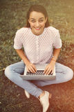 Young woman with laptop sitting on grass Stock Photo