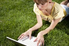 Young woman with laptop sitting on green grass Stock Photo