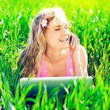Young woman with laptop sitting on green grass Royalty Free Stock Image