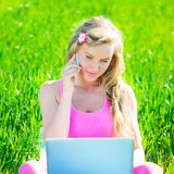 Young woman with laptop sitting on green grass Royalty Free Stock Photography