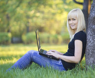 Young woman with laptop. Sitting on green grass Royalty Free Stock Photo