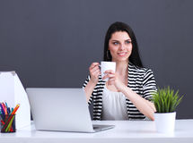Young woman with a laptop sitting isolated on grey background. Portrait of young woman with a laptop sitting isolated on grey background Royalty Free Stock Photo