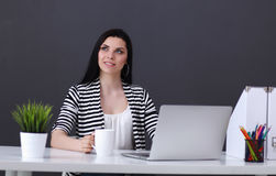 Young woman with a laptop sitting isolated on grey Stock Photo