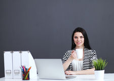 Young woman with a laptop sitting isolated on grey Royalty Free Stock Photos
