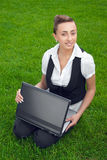 Young woman with laptop sitting on lawn. Happy businesswoman with laptop sitting on green lawn stock photos