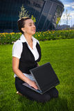 Young woman with laptop sitting on lawn. Businesswoman with laptop sitting on green lawn in park royalty free stock photography