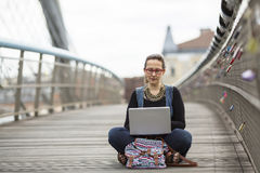 Young woman with laptop sitting on a pedestrian bridge. Stock Photography