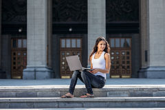 A young woman with a laptop sitting on the stairs, near the univ. Young girl sitting on the street in the park, working and communicating online Royalty Free Stock Photo