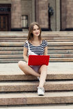 Young woman with laptop sitting on stairs near the university. Young woman with a laptop sitting on the stairs, near the university Stock Photography
