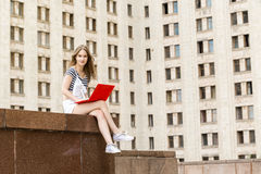 Young woman with laptop sitting on stairs near the university. Young woman with a laptop sitting on the stairs, near the university Stock Image