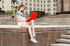 Young woman with laptop sitting on stairs near the university. Young woman with a laptop sitting on the stairs, near the university Royalty Free Stock Photos