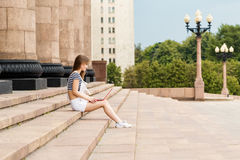 Young woman with laptop sitting on stairs near the university. Young woman with a laptop sitting on the stairs, near the university Royalty Free Stock Images
