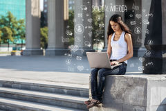 Young woman with laptop sitting on the stairs, near university Royalty Free Stock Photography