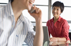Young woman with laptop, smiling at man using telephone, focus on woman Stock Photos