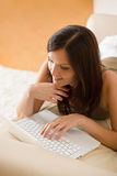 Young woman with laptop on sofa home Stock Photography