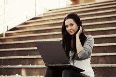 Young woman with laptop on the steps Royalty Free Stock Photo