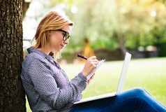 Young woman with a laptop studying outdoors. Royalty Free Stock Photos