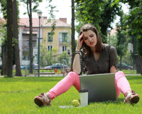 Young Woman with Laptop. Young woman thinking in front of a laptop outside in an urban park Royalty Free Stock Photos