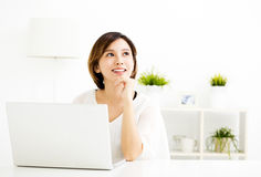 Young woman with laptop and thinking in living room Stock Photo
