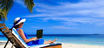 Young woman with laptop on tropical beach Stock Images