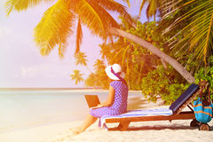 Young woman with laptop on tropical beach Royalty Free Stock Images