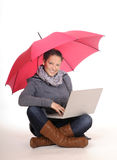 Young woman with laptop and umbrella Stock Image