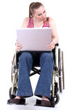Young woman with laptop on the wheelchair Stock Photography