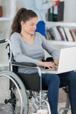 Young woman with laptop on wheelchair Royalty Free Stock Photo