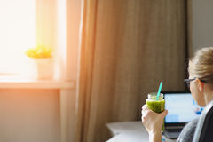 Young woman with laptop at wooden table. Drinking green smoothie. Stock Photography