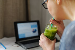 Young woman with laptop at wooden table. Drinking green smoothie. Stock Photos