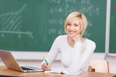 Young Woman With Laptop Writing Notes At Desk royalty free stock photo