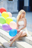 A young woman with large colourful latex balloons Royalty Free Stock Images