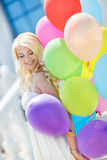 A young woman with large colourful latex balloons Stock Image