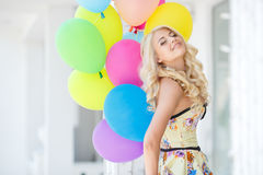 A young woman with large colourful latex balloons Royalty Free Stock Image