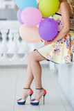 A young woman with large colourful latex balloons Stock Photography