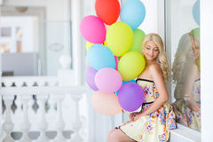 A young woman with large colourful latex balloons Stock Images