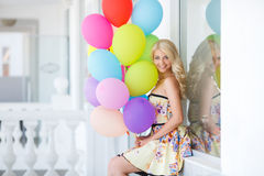 A young woman with large colourful latex balloons Royalty Free Stock Photography