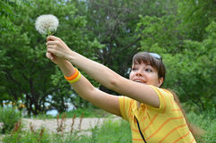 Young woman with large dandelion Stock Photo