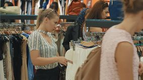 A young woman in a large store chooses new clothes for herself stock footage